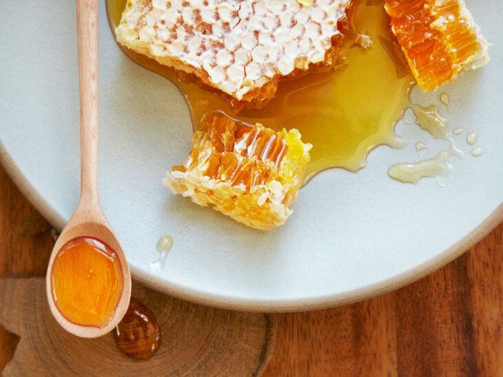 сотовый мед с ложкой на тарелке