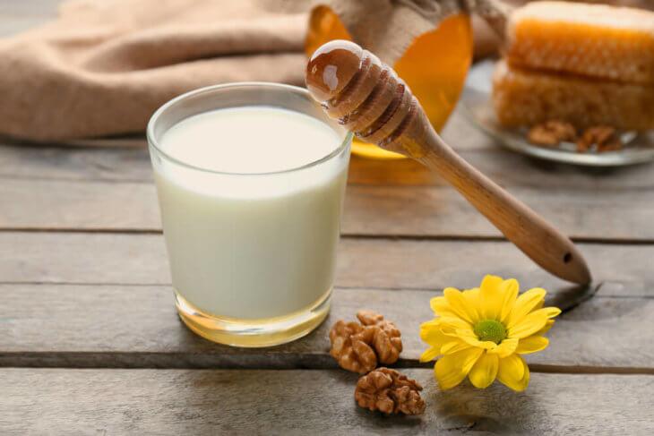 стакан молока с медом и ложкой